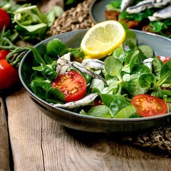 Salada verde com anchovas em conserva ou filé de sardinha e tomate cereja, servida em uma tigela azul com limão e azeite de oliva
