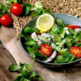 Salada verde com anchovas em conserva ou filé de sardinha e tomate cereja, servido em uma tigela azul com limão e azeite no guardanapo de palha sobre a velha mesa de madeira. imagem quadrada