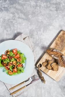Salada verde com camarão grelhado e placa de corte de madeira com pão.