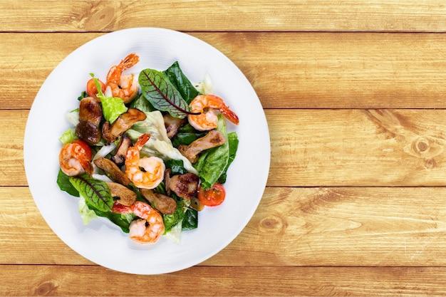 Salada verde com camarão no fundo