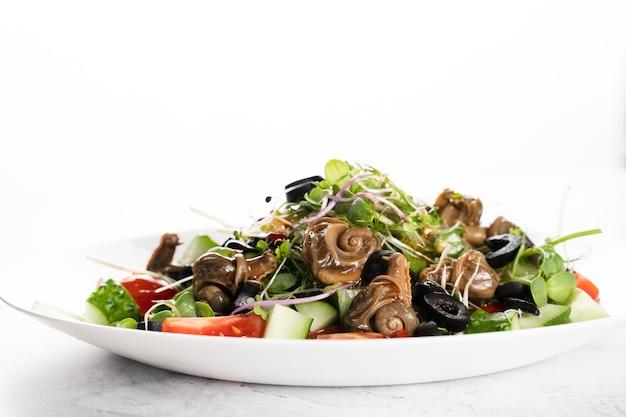 Salada verde com caracóis em fundo branco. cozinha gourmet francesa.