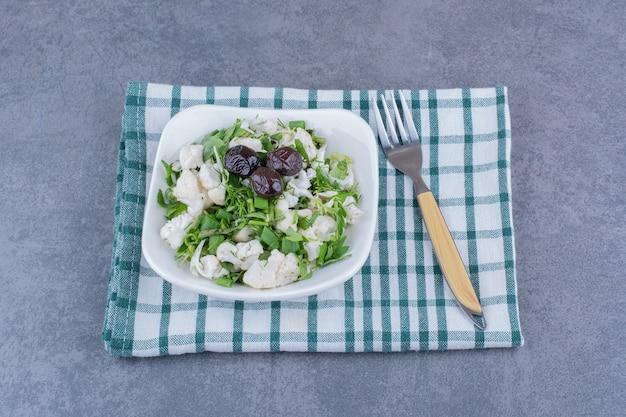 Salada verde com ervas e couve-flor em uma tigela de cerâmica