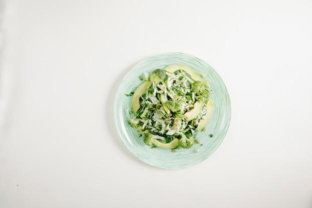 Salada verde com ervas e queijo picado.