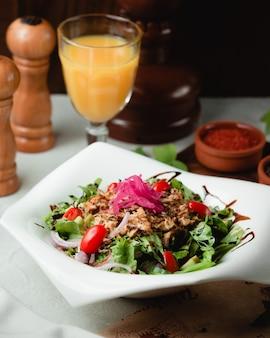 Salada verde com ervas e tomate, com um copo de suco de laranja.
