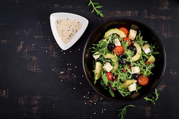 Salada verde com fatias de abacate, tomate cereja, azeitonas pretas e queijo