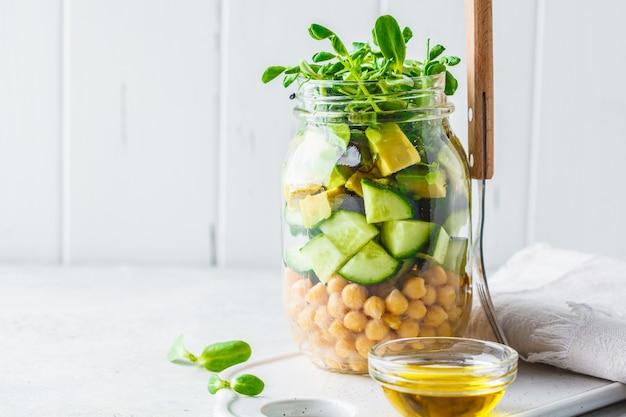 Salada verde com grãos-de-bico em um frasco, fundo branco, espaço da cópia.