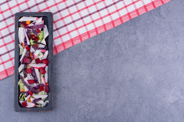 Salada verde com ingredientes em uma travessa preta.