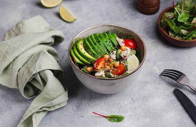 Salada verde com rúcula, abacate, grão de bico, alcaravia, acelga, tomate, limão, queijo cottage, sementes de linho e gergelim, azeite de oliva na parede cinza com guardanapo de linho verde. vista superior com copyspace
