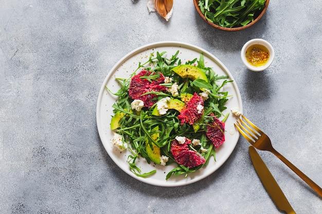Salada verde com rúcula, laranja pigmentada, abacate, queijo cottage grelhado na parede de pedra azul com garfo e faca pretos. conceito de alimentação saudável. flatlay com copyspace