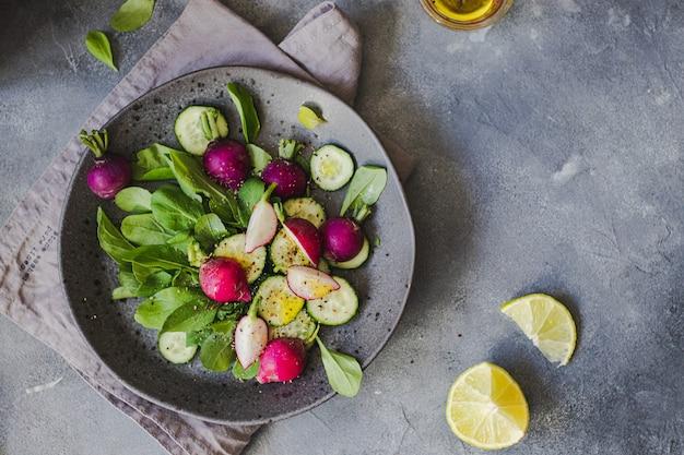 Salada verde com rúcula, pepino, rabanete, limão, azeite de oliva, ervas grelhadas no fundo de pedra cinza