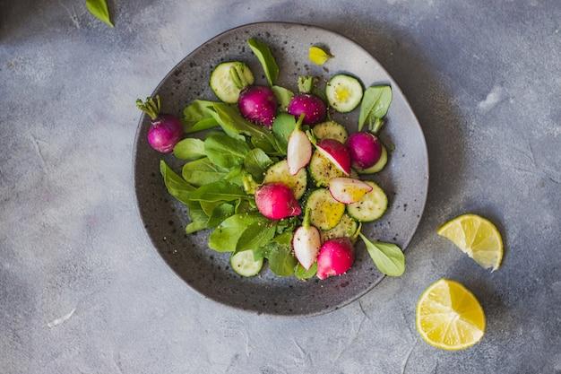 Salada verde com rúcula, rabanete, pepino e azeite. conceito de comida saudável.