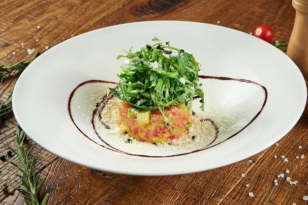 Salada verde com rúcula, salmão levemente salgado, abacate e parmesão em uma tigela branca sobre uma superfície de madeira em uma composição com especiarias