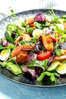Salada verde com tomate cereja, pepino, abacate, ovos e camarões defumados, verduras mistas. comida saudável. comer limpo. fundo de receita de comida. fechar-se.