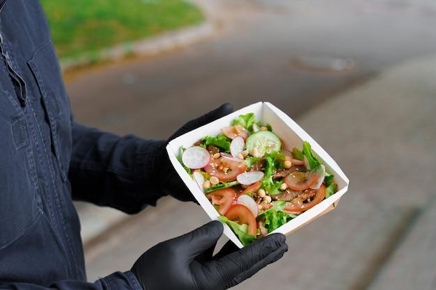 Salada verde com vitela e vagantes. entrega segura com máscara e luvas médicas pretas em quarentena. salada em caixa térmica ecológica.