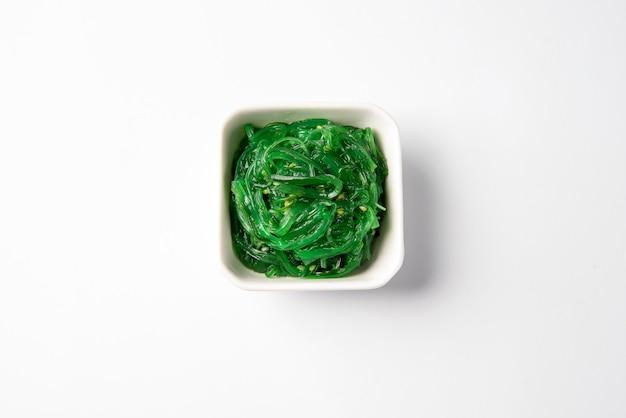 Salada verde da alga de chuka isolada na vista superior de superfície branca. erva daninha do mar de chukka, comida saudável de algas