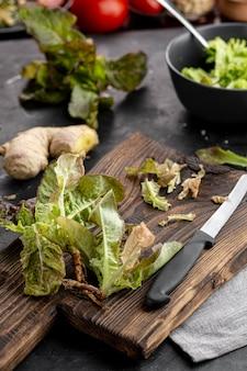 Salada verde de alta vista na placa de madeira