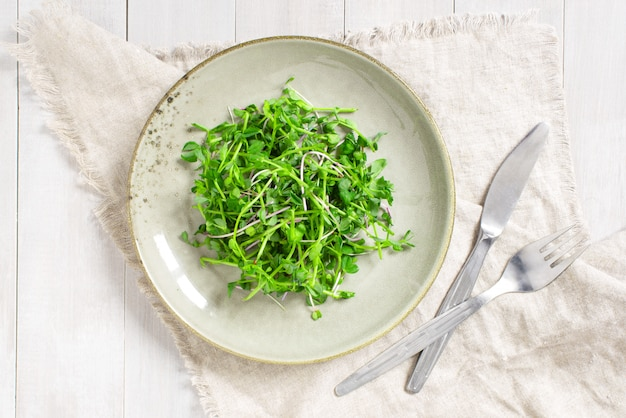 Salada verde de mudas no prato na mesa branca