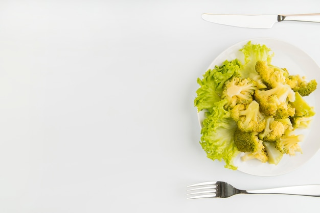 Salada verde de vista superior com talheres e cópia-espaço