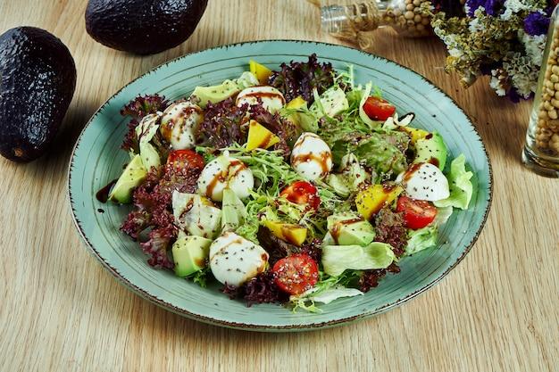 Salada verde e suculenta com fazenda mussarela, alface, sementes de gergelim, tomate cereja e abacate em uma tigela azul em uma mesa de madeira. comida saudável. nutrição fitness. saboroso close-up