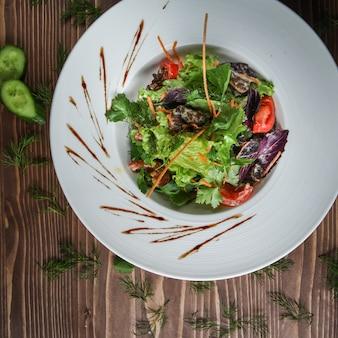 Salada verde em um prato com ervas, pepino, tomate, cenoura