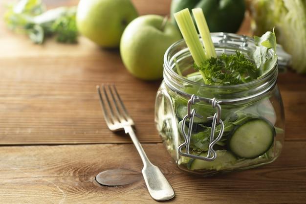 Salada verde embalada no frasco de pedreiro. saudável, caseiro, leve comida. copie o espaço.