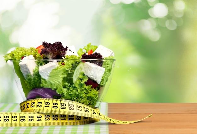 Salada verde fresca e fita métrica no fundo