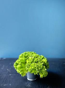 Salada verde fresca em um pequeno balde na mesa rústica branca