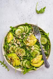 Salada verde saudável com abacate, pepino e rúcula no prato branco.