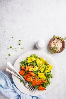 Salada verde saudável da couve com abacate e as batatas doces cozidas.