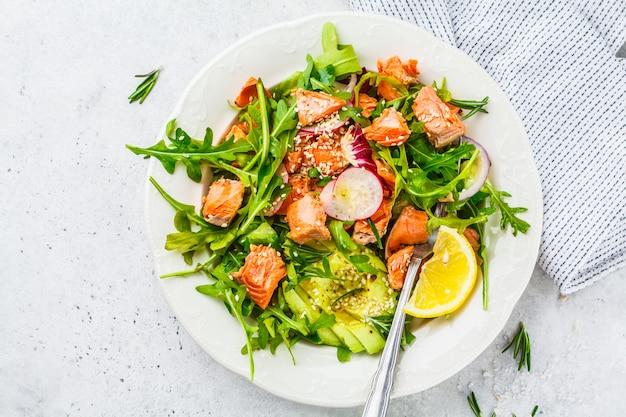 Salada vermelha cozida dos peixes com abacate, pepino, rabanete e rúcula na placa branca, vista superior.