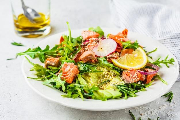 Salada vermelha cozida dos peixes com abacate, pepino, rabanete e rúcula na placa branca.