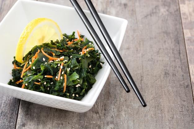 Salada wakame com cenoura, sementes de gergelim e suco de limão em uma tigela na mesa de madeira