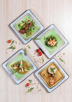 Saladas com carne, frango e peixe em placas quadradas brancas na mesa de madeira clara em um resta