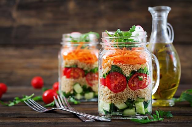 Saladas com quinoa, rúcula, rabanete, tomate e pepino em potes de vidro nas costas de madeira