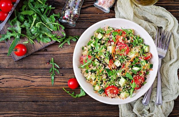 Saladas com quinoa, rúcula, rabanete, tomate e pepino em tigela sobre fundo de madeira.