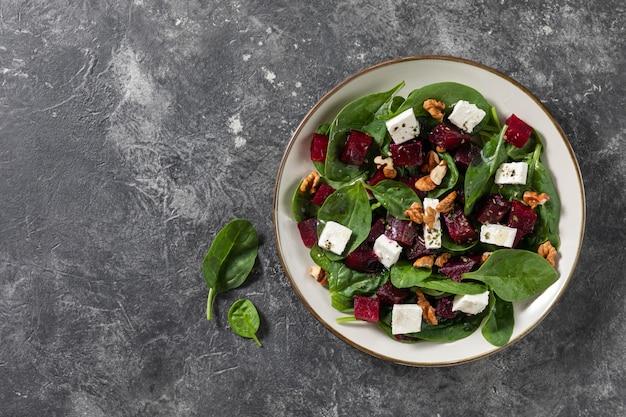 Saladas de carpaccio de beterraba vegetariana com espinafre, manjericão, azeite, queijo de cabra, nozes. vista superior, espaço. alimentação saudável.