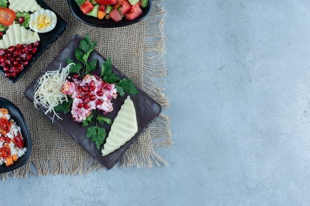 Saladas diferentes em travessas em mármore.