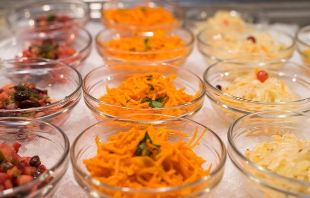 Saladas em tigelas na cozinha aberta do restaurante estão em fila