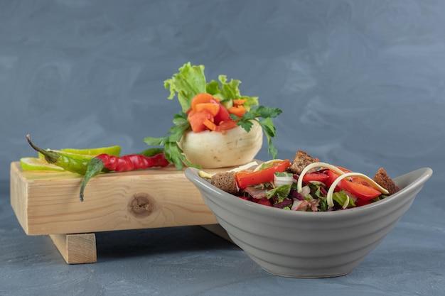 Saladeira cinza ao lado de um molho de legumes em uma placa de madeira na mesa de mármore.