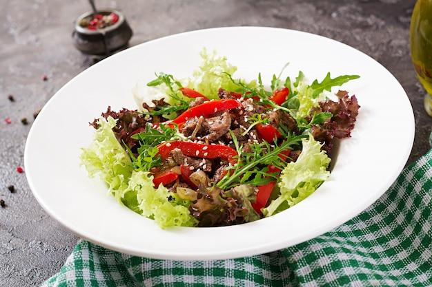 Saladeira com carne de bovino, pimentos, cebolas e verduras mistas, alface, rúcula