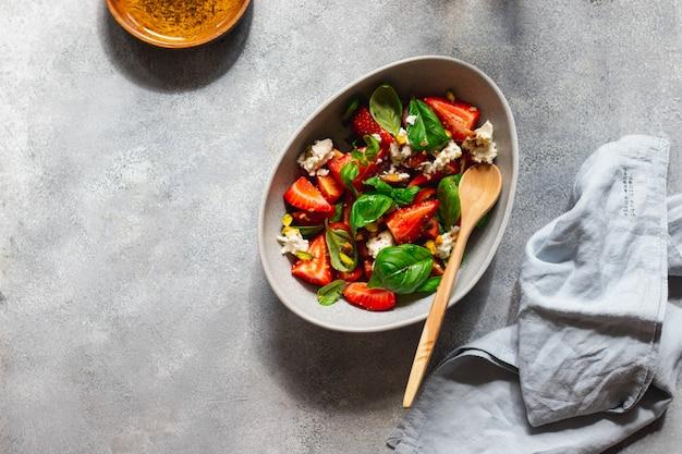 Saladeira com manjericão verde, morango, tomate, queijo cottage, pistache e azeite de oliva com ervas grelhadas na parede cinza com colher de pau. conceito de alimentação saudável. flatlay com copyspace.