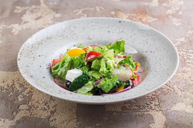 Saladeira grega com queijo feta, tomate, pimentão e azeitonas em um prato branco sobre a mesa de um restaurante. composição horizontal