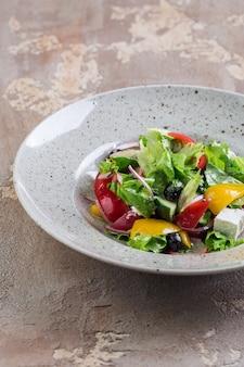 Saladeira grega com queijo feta, tomate, pimentão e azeitonas em um prato branco sobre a mesa de um restaurante. composição vertical