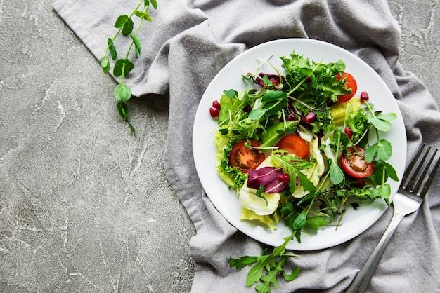 Saladeira mista verde fresca com tomates e microgreens na mesa de concreto. alimentação saudável, vista superior.