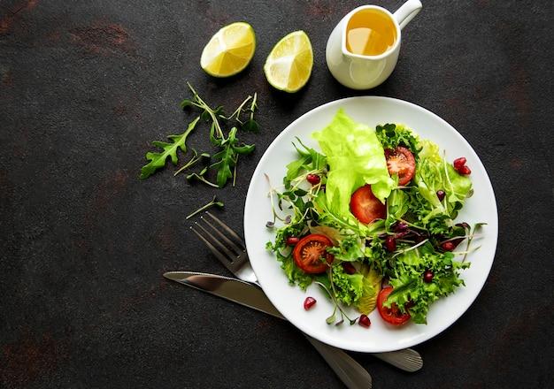 Saladeira mista verde fresca com tomates e microgreens na mesa de concreto preto. alimentação saudável, vista superior.