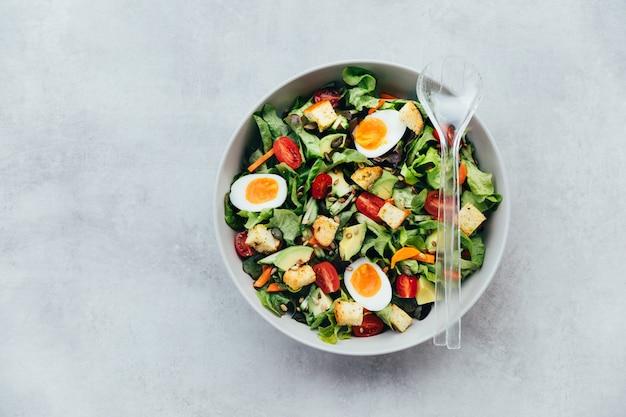 Saladeira saudável com ovos, abacate e tomate polvilhado com sementes de girassol e abóbora.