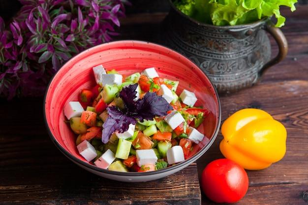 Saladlettuce grego de vista lateral, tomate, queijo feta, pepinos, azeitonas pretas, cebola roxa na mesa de madeira escura