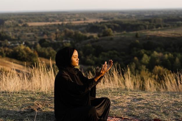 Salah. mulher africana com manto preto sentado no tapete e orar em deus. religião islâmica