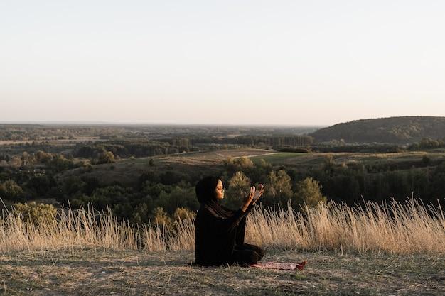 Salah tradicional orando a deus no tapete. mulher muçulmana negra orando a alá.