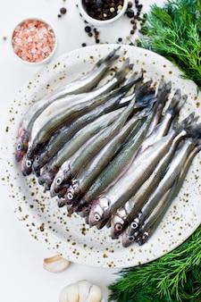 Salakas crus em um prato, endro, sal rosa, pimenta e alho